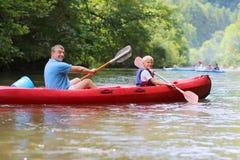 Padre e hijo kayaking en el río Fotos de archivo