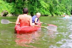 Padre e hijo kayaking en el río Foto de archivo