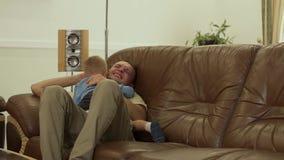 Padre e hijo que abrazan en el sofá almacen de metraje de vídeo
