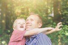 Padre e hijo que abrazan y que miran el sol imagenes de archivo