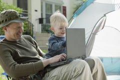 Padre e hijo que acampan con la computadora portátil Fotos de archivo libres de regalías