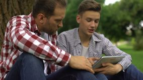 Padre e hijo que buscan recambios del coche conveniente en línea, uso de la búsqueda almacen de metraje de vídeo