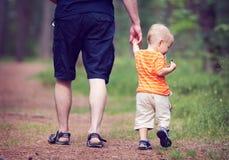 Padre e hijo que caminan en el bosque Fotos de archivo