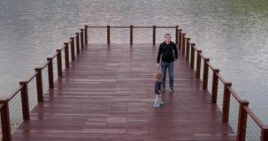 Padre e hijo que caminan en el puente almacen de video