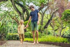 Padre e hijo que caminan en un pavimento de adoquín texturizado, Reflexolog Imagenes de archivo