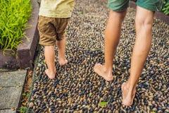 Padre e hijo que caminan en un pavimento de adoquín texturizado, Reflexolog Fotos de archivo