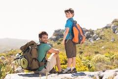 Padre e hijo que caminan a través de las montañas Fotografía de archivo