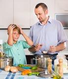 Padre e hijo que cocinan la cena Imagen de archivo libre de regalías
