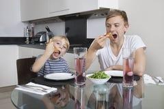 Padre e hijo que comen la pizza en la mesa de desayuno Foto de archivo