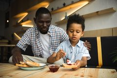 Padre e hijo que comen tostadas Foto de archivo libre de regalías