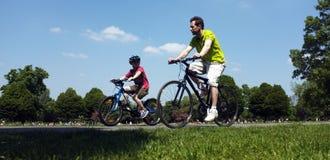 Padre e hijo que completan un ciclo en el parque Foto de archivo libre de regalías