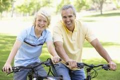 Padre e hijo que completan un ciclo a través de un parque Foto de archivo
