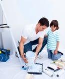 Padre e hijo que consiguen listos para pintar un cuarto Foto de archivo
