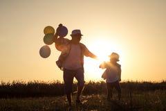 Padre e hijo que corren en el camino en el tiempo de la puesta del sol Fotos de archivo
