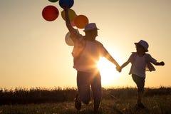 Padre e hijo que corren en el camino en el tiempo de la puesta del sol Fotografía de archivo libre de regalías