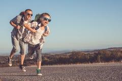 Padre e hijo que corren en el camino en el tiempo del día Fotografía de archivo