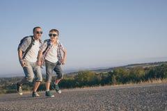 Padre e hijo que corren en el camino en el tiempo del día Foto de archivo libre de regalías