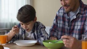 Padre e hijo que desayunan junto, comiendo el hogar sabroso de la mañana de los copos de maíz almacen de video