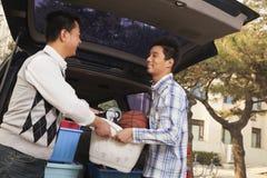 Padre e hijo que desempaquetan el coche para la universidad fotos de archivo libres de regalías