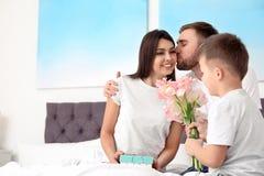 Padre e hijo que felicitan a la mam? en casa D?a feliz del `s de la madre fotografía de archivo libre de regalías