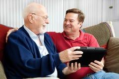 Padre e hijo que gozan de la PC de la tablilla Imágenes de archivo libres de regalías