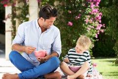 Padre e hijo que gozan del cereal de desayuno al aire libre imagenes de archivo
