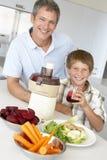 Padre e hijo que hacen el jugo de las verduras frescas