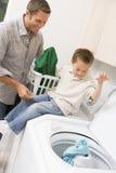 Padre e hijo que hacen el lavadero Imagenes de archivo