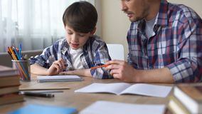 Padre e hijo que hacen la preparación junta, papá que explica la tarea, educación escolar almacen de video