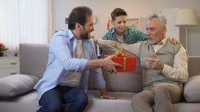 Padre e hijo que hacen la sorpresa del cumpleaños para el abuelo mayor, dando la caja de regalo almacen de metraje de vídeo