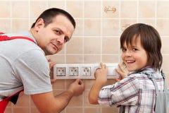 Padre e hijo que instalan los accesorios eléctricos de la pared Imagenes de archivo