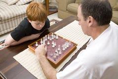 Padre e hijo que juegan a ajedrez dentro imágenes de archivo libres de regalías
