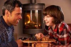 Padre e hijo que juegan a ajedrez por el fuego de registro acogedor Imágenes de archivo libres de regalías
