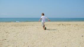 Padre e hijo que juegan así como bola en fútbol en la playa bajo fondo de la puesta del sol almacen de video