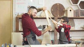 Padre e hijo que juegan a caballeros con las espadas de madera de DIY en el taller del carpintero almacen de metraje de vídeo