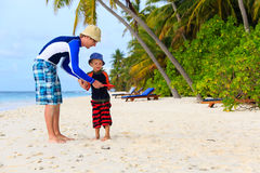 Padre e hijo que juegan con el disco de vuelo en la playa Imágenes de archivo libres de regalías