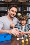 Padre e hijo que juegan con el modelo de los átomos Foto de archivo libre de regalías