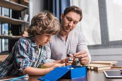 Padre e hijo que juegan con el modelo de los átomos Imagen de archivo
