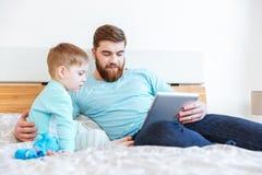 Padre e hijo que juegan con la tableta en cama Foto de archivo