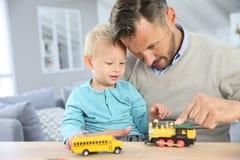 Padre e hijo que juegan con los juguetes del coche fotos de archivo