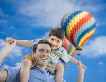 Padre e hijo que juegan a cuestas con los globos del aire caliente detrás fotografía de archivo