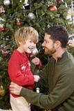 Padre e hijo que juegan delante del árbol de navidad Fotografía de archivo