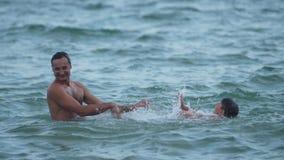 Padre e hijo que juegan en el mar que salta en el vídeo de la cámara lenta del agua almacen de video