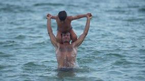 Padre e hijo que juegan en el mar que salta en el vídeo de la cámara lenta del agua almacen de metraje de vídeo