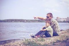 Padre e hijo que juegan en el parque cerca del lago en el tiempo del día Imagenes de archivo