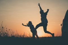 Padre e hijo que juegan en el parque en el tiempo de la puesta del sol Imagenes de archivo