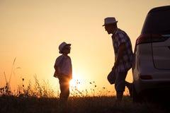 Padre e hijo que juegan en el parque en el tiempo de la puesta del sol Fotografía de archivo