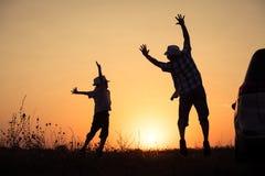 Padre e hijo que juegan en el parque en el tiempo de la puesta del sol Imagen de archivo libre de regalías
