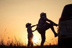 Padre e hijo que juegan en el parque en el tiempo de la puesta del sol Foto de archivo