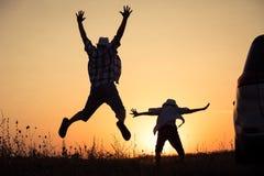 Padre e hijo que juegan en el parque en el tiempo de la puesta del sol Fotos de archivo